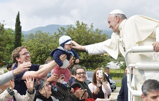 Pope Francis reaching out to blessing a baby in the crowd